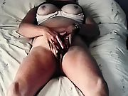 Tanned milf kneading her love button on her bed