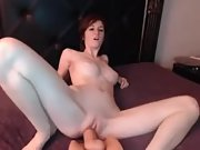 Busty sandy-haired smashing a huge dildo on the webcam